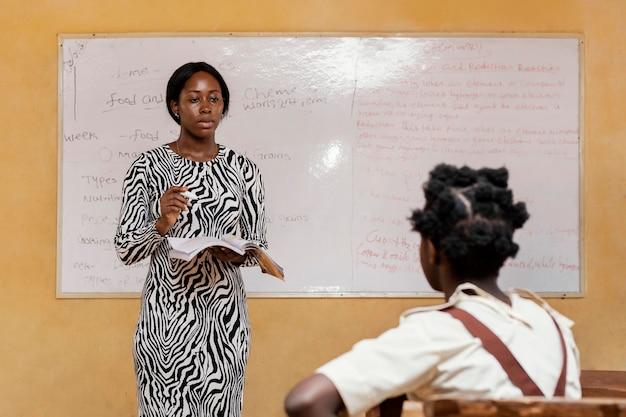 Femme enseignant aux enfants en classe