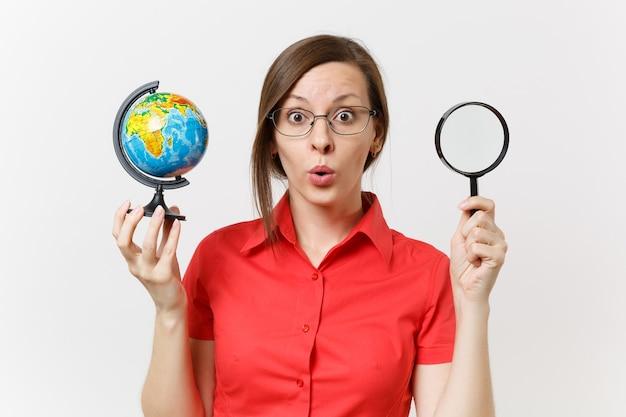 Femme enseignante d'affaires étonnée en chemise rouge tenant et regardant à travers une loupe sur un globe isolé sur fond blanc. enseignement de l'éducation dans le concept d'université de lycée. espace de copie.
