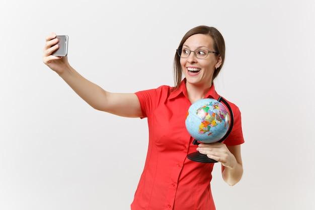 Femme enseignante d'affaires souriante en chemise rouge tenant un téléphone portable et faisant une prise de selfie avec un globe isolé sur fond blanc. enseignement de l'éducation dans le concept d'université de lycée. espace de copie.