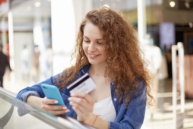 Une femme ensoleillée de bonne humeur festive va faire un cadeau, pour cela, elle a pris une carte de crédit et regarde dans le téléphone avec un étui bleu pour vérifier combien d'argent