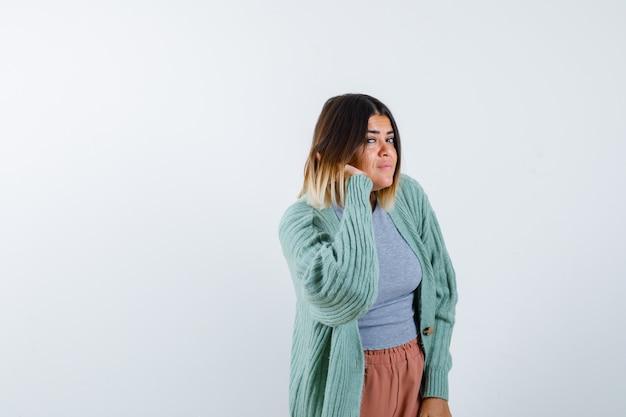 Femme entendant une conversation privée dans des vêtements décontractés et à la curieuse, vue de face.