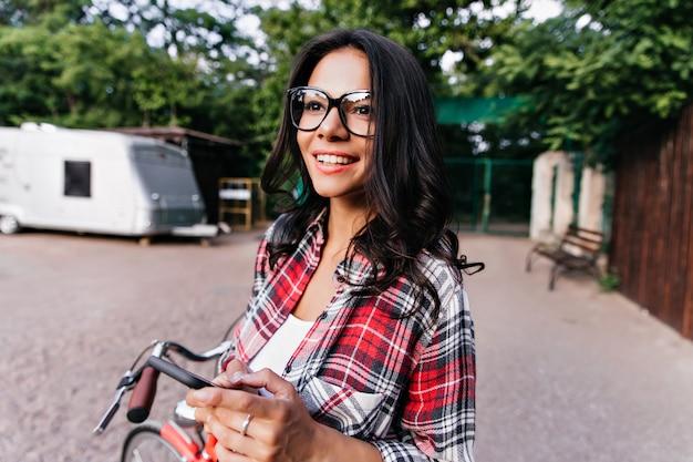 Femme enthousiaste avec anneau rêveur à la recherche de la nature. magnifique fille caucasienne posant avec plaisir dans la rue au matin de printemps.