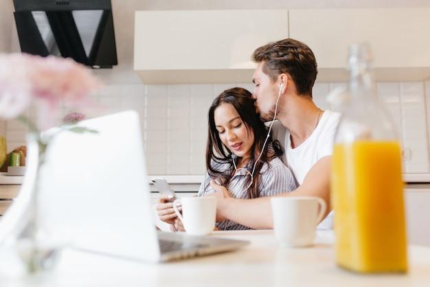 Femme enthousiaste à l'écoute de la musique et à l'aide de smartphone pendant que son petit ami l'embrasse