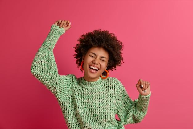 Une femme enthousiaste à la peau sombre bouge au rythme de la musique, garde les bras levés, profite d'une fête ou d'un festival génial, vêtue d'un pull en tricot, essaie d'oublier les problèmes quotidiens, s'amuse, pose à l'intérieur