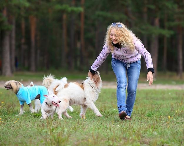 Une femme entraîne des chiens dans le parc