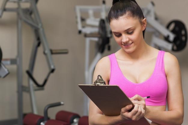 Femme entraîneur écrit sur le presse-papiers dans une salle de sport