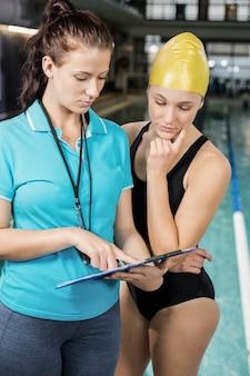 Femme entraîneur montrant le presse-papiers chez un nageur à la piscine
