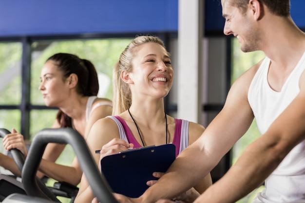 Femme entraîneur parlant avec un homme faisant du vélo d'exercice au gymnase