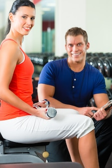 Femme et entraîneur personnel dans une salle de sport avec des haltères