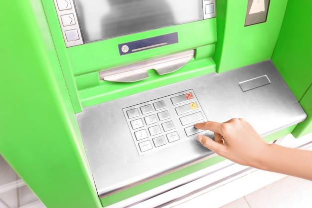 Femme entrant le code pin du distributeur automatique de billets