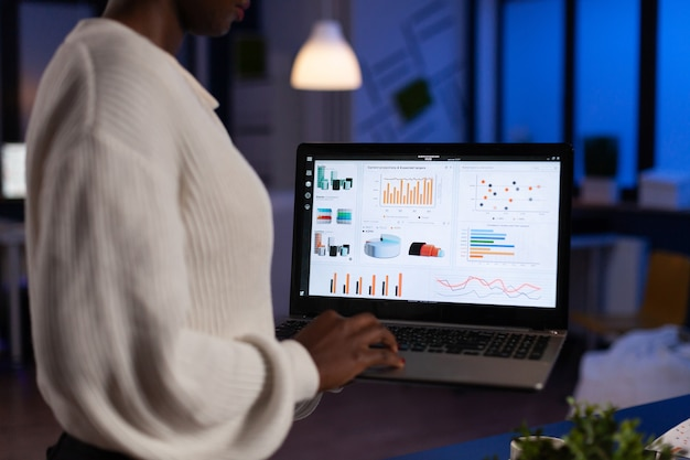 Femme d'entrepreneur afro-américaine analysant des graphiques financiers