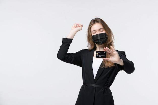 Femme entrepreneur ambitieuse en costume portant son masque médical et montrant une carte bancaire sur blanc