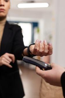 Femme entrepreneur dans la construction d'un bureau utilisant le paiement sans contact d'une montre connectée pour la livraison de nourriture. femme d'affaires en démarrage d'entreprise recevant un sac de nourriture.