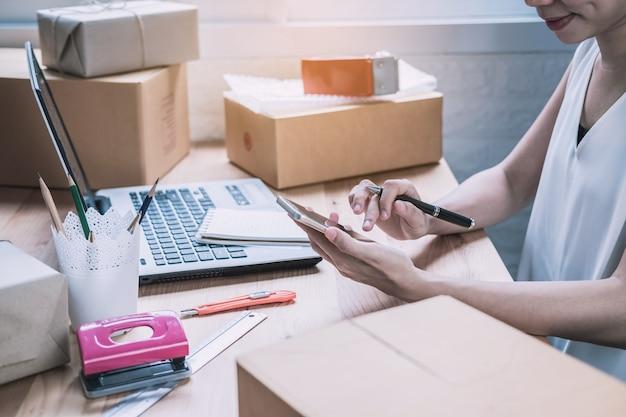 Femme entrepreneur jeune startup entreprise travaillant avec un téléphone intelligent à la maison