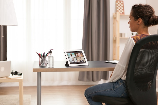 Femme entrepreneur lors d'un appel vidéo sur tablette au bureau à domicile.