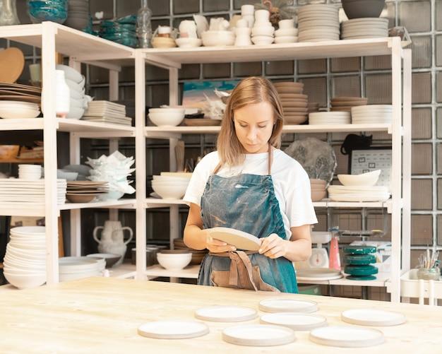 Femme entrepreneur avec ordinateur portable dans l'atelier de travail artisanal