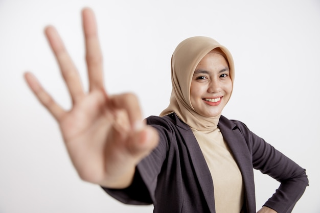 Femme entrepreneur portant le hijab ok signe main pose, mur blanc isolé