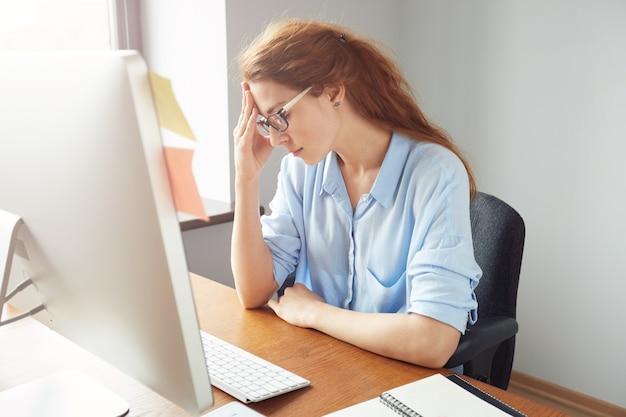 Femme entrepreneur préoccupée regardant l'écran de l'ordinateur tout en travaillant au bureau