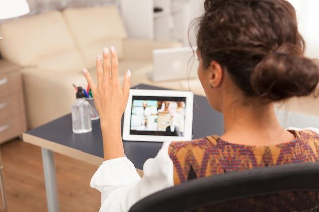 Femme entrepreneur saluant dans un appel vidéo du bureau à domicile.