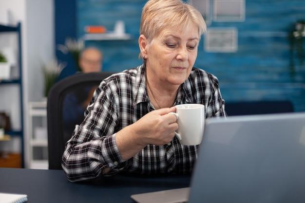 Femme entrepreneur senior lisant sur ordinateur savourant une tasse de café et son mari et lisant un livre