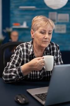Femme entrepreneur senior lisant sur ordinateur