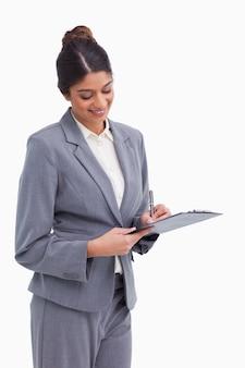 Femme entrepreneur souriant, prendre des notes sur le presse-papiers