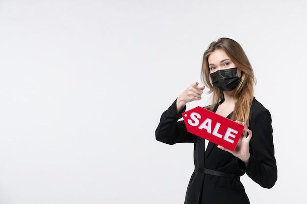 Femme entrepreneur souriante en costume portant son masque médical et montrant une vente pointant quelque chose sur un blanc isolé