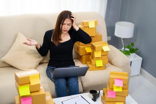 Femme entrepreneur stressée travaillant avec un ordinateur portable et a des problèmes pour vendre des produits en ligne au bureau à domicile