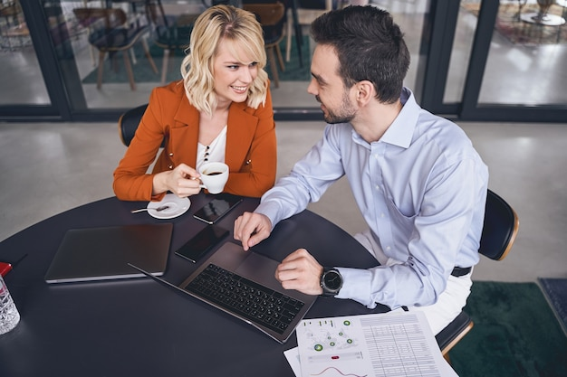 Femme entrepreneur avec une tasse d'espresso en regardant son collègue masculin souriant au bureau
