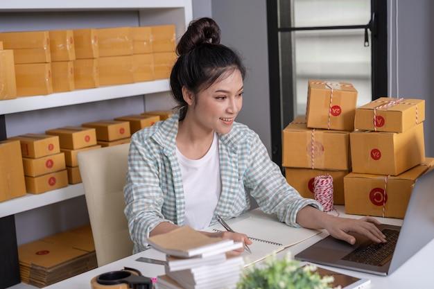 Femme entrepreneur vérifiant et en passant commande avec du carton
