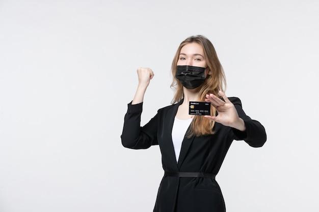 Femme entrepreneure ambitieuse en costume portant son masque médical et montrant une carte bancaire profitant de son succès sur blanc