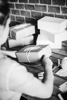Femme enveloppant elle-même un paquet