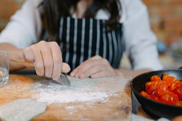 Femme enveloppée dans des boulettes cuisinier de cuisine asiatique.