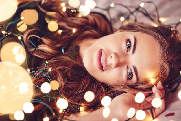 Femme enveloppée de lumières de noël couchée sur le dos