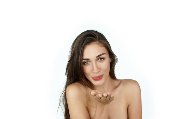 Femme envoie un baiser d'air debout sur fond blanc