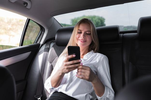 Femme envoyant des sms sur le siège arrière de la voiture