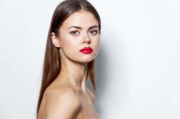 Femme épaules nues attrayant peau claire regard lèvres rouges fond clair
