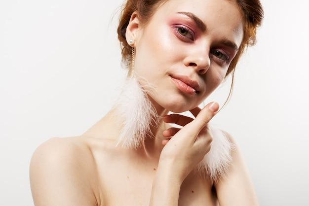 Femme épaules nues boucles d'oreilles moelleuses cosmétiques pour la peau pure. photo de haute qualité