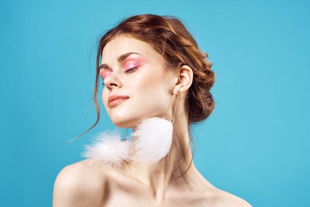 Femme épaules nues boucles d'oreilles moelleuses mode maquillage lumineux fond bleu