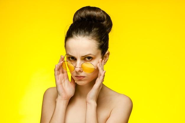 Femme épaules nues surpris regard jaune lunettes fond isolé. photo de haute qualité