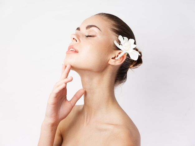Femme épaules nues yeux fermés studio de charme fleur blanche. photo de haute qualité