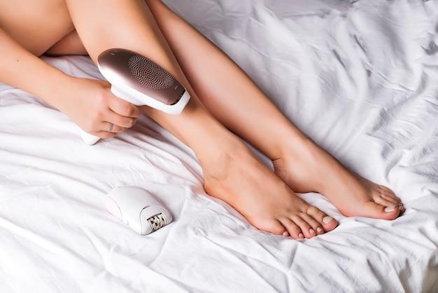 Femme épilant à la maison avec un équipement spécial sur un lit
