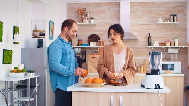 Femme épluchant des oranges pour un smoothie nutritif dans la cuisine. mari portant une chemise en jean. joyeuse famille faisant ensemble du jus savoureux nutritif frais et sain pour le petit-déjeuner à partir de fruits frais