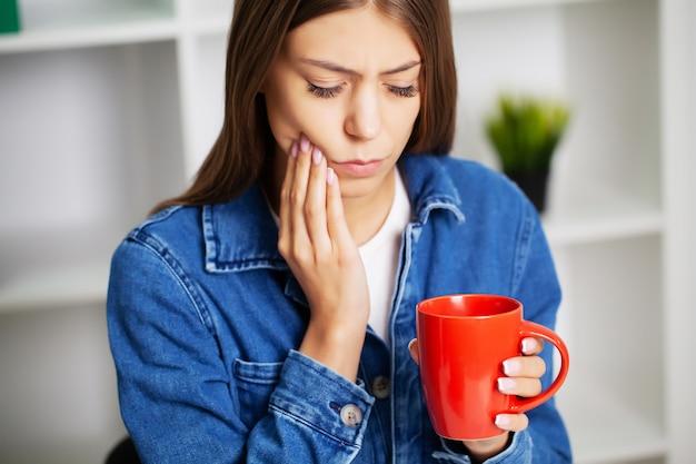 Femme épuisée au bureau souffrant de graves maux de dents