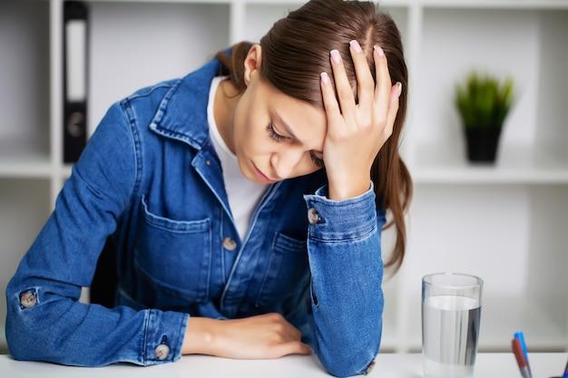Femme épuisée au bureau souffrant de graves maux de tête