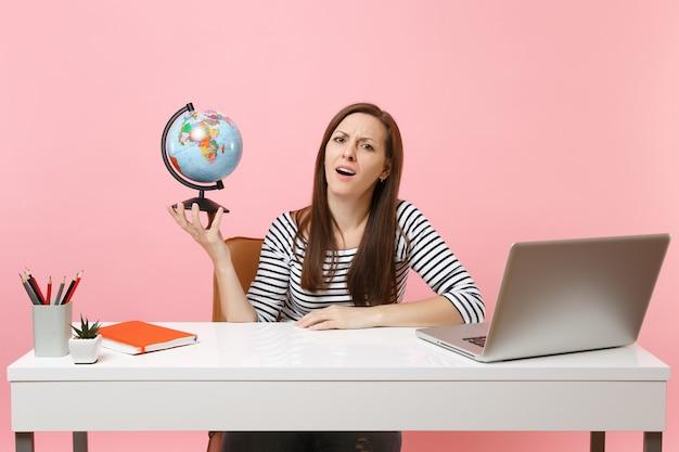 Une femme épuisée et bouleversée tenant un globe ayant des problèmes avec la planification des vacances tout en étant assise, travaille au bureau avec un ordinateur portable isolé sur fond rose pastel. concept de carrière d'entreprise de réalisation. espace de copie.