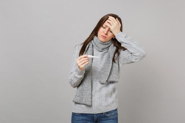 Femme épuisée en pull, foulard mis la main sur le front, tenir à la recherche sur le thermomètre isolé sur fond gris. mode de vie sain, traitement des maladies malades, concept de saison froide. maquette de l'espace de copie.