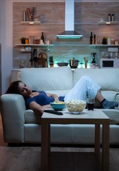 Femme épuisée regardant une émission de télévision allongée sur un canapé dans le salon. une jeune femme fatiguée et malheureuse en pyjama se reposant sur un canapé confortable devant la télévision s'ennuyant à manger des collations tard dans la nuit
