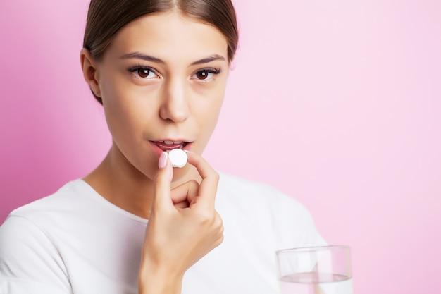 Une femme épuisée souffrant de maux de dents prend un analgésique