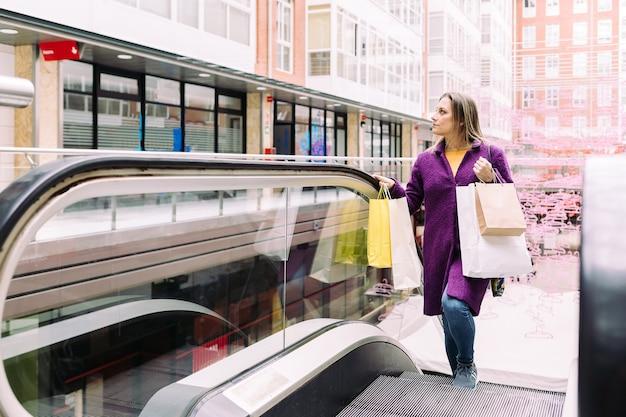 Femme sur un escalator avec des sacs à provisions dans ses mains